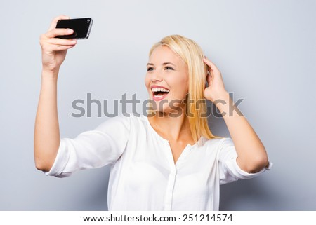 Expert in photography. Cheerful young blond hair woman holding mobile phone and making photo of herself while standing against grey background - stock photo