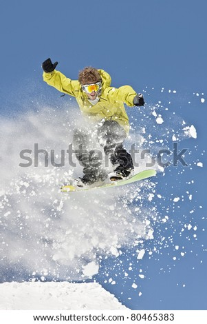 Expert male snowboarder making jump in powder snow.