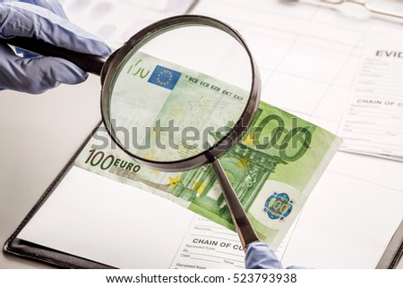 Expert with magnifying glass checks suspicious money