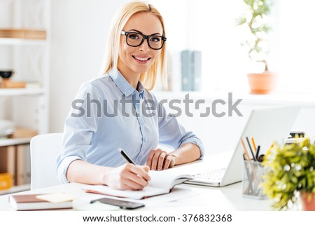 Expertise in her business. Cheerful young beautiful woman making some notes and looking at camera with smile while sitting at her working place - stock photo