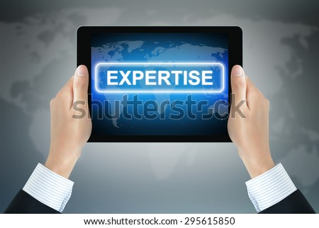 EXPERTISE sign on tablet pc screen held by businessman hands - stock photo
