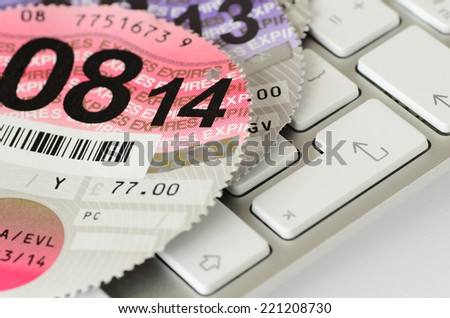 Expired UK vehicle tax disc on a keyboard.