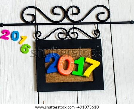Expiring 2016.New year 2017, the figures in the picture frame on white wooden background.