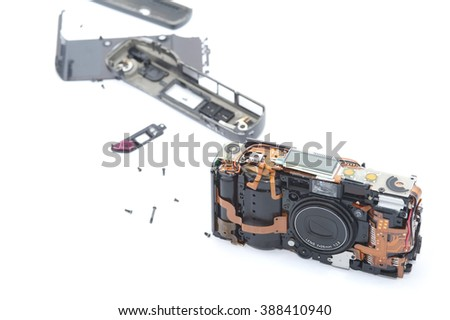 Exploded or dismantled camera laying on white background with various pieces trailed behind it - stock photo