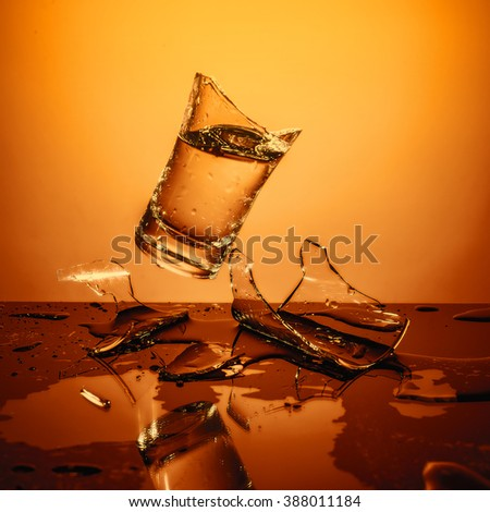 Exploding Glass cup with water shattering over orange background, crash and splashes - stock photo
