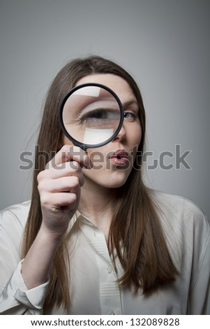 Explore. Young woman looking through magnifier