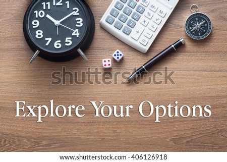 Explore Your Options written on wooden table with clock,dice,calculator pen and compass - stock photo