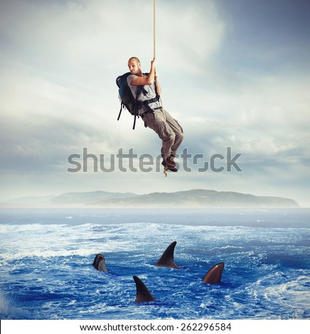 Explorer frightened by hungry sharks under him - stock photo