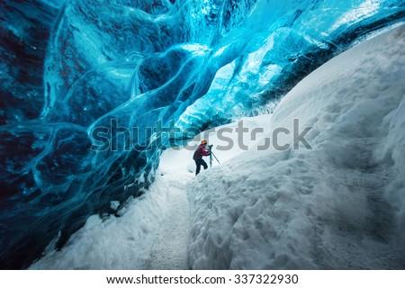 Explorer inside ice cave at Vatnajokull glacier, Iceland - stock photo