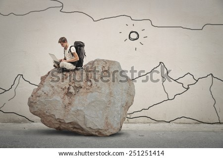 Explorer sitting on top of a rock  - stock photo