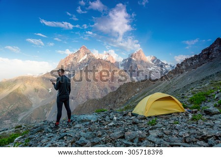 Explorer talking on satellite phone. Silhouette of man in wild mountain landscape walk along yellow camping tent holding radio transmitter connection with team blue sky sunny evening - stock photo