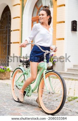 Exploring new places. Attractive young smiling woman riding a vintage bike and looking  - stock photo
