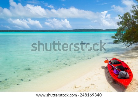 Exploring the  gorgeous lagoon of Aitutaki, Cook Islands, by canoeing is the best way to reach little desert islands like this. Adventure concept in exotic places. - stock photo