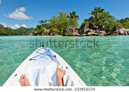 Exploring the Port Launay Marine National Park, Seychelles in a canoe or kayak with a view of the kayakers bare feet in the prow - stock photo