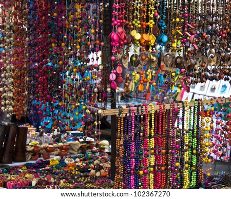 Explosion of vibrant color in beads hanging on display in outdoor market