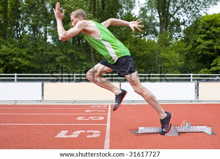 Explosive start of an Athlete leaving the starting blocks on a sprint run