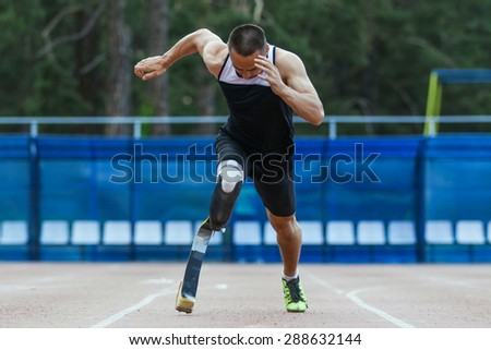 Explosive start of athlete with handicap at the stadium - stock photo