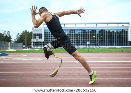 Explosive start of athlete with handicap at the stadium - stock photo
