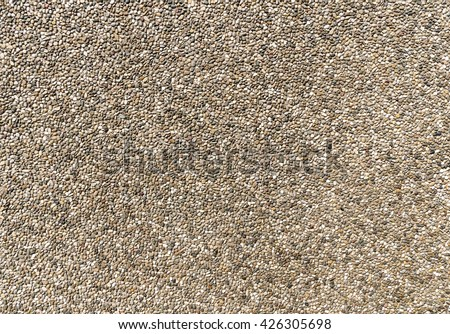 Exposed aggregate concrete in closeup made of small pebbles in different brown and gray color shades  - stock photo