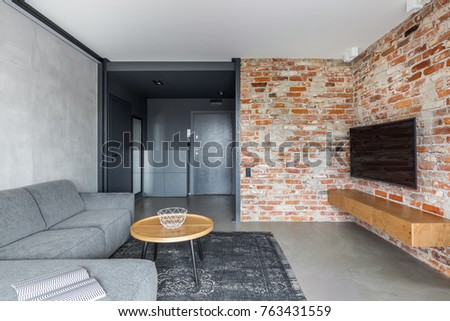 Exposed Brick Wall And Concrete Floor In Industrial Living Room