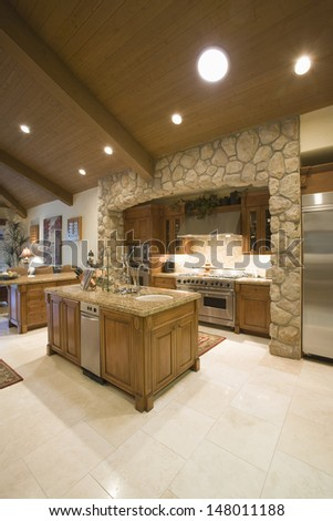 Exposed stone kitchen surround with spotlights on wooden ceiling - stock photo