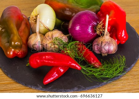Exposition of fresh organic vegetables, Healthy food, Healthcare, carrot,garlic, onion, walnuts, red onion, red pepper, dill, fennel, red hot chili pepper on black stone table.