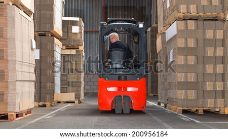 Expreinced forklift driver is driving his forklift backwards trough piled pallets with  cardboardboxes stack on it.  - stock photo