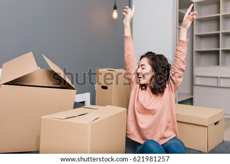 Expressing brightful true emotions, positivity of young pretty woman with short brunette curly hair on bed surround carton boxes in modern apartment. Enjoying moving, happiness at new home