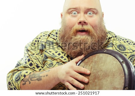 Expressing himself in music. Closeup image of funny bearded man with surprised face expression holding African drums while standing isolated over white background