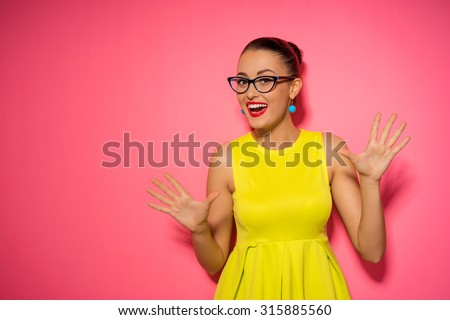 Expressing joy! Happy pretty young woman in yellow dress. Pink background. - stock photo