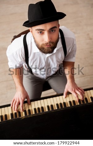 Expressing myself with music. Top view of handsome bearded young men playing piano and looking at camera - stock photo