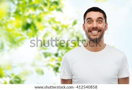 expression and people concept - man with funny face over green natural background - stock photo