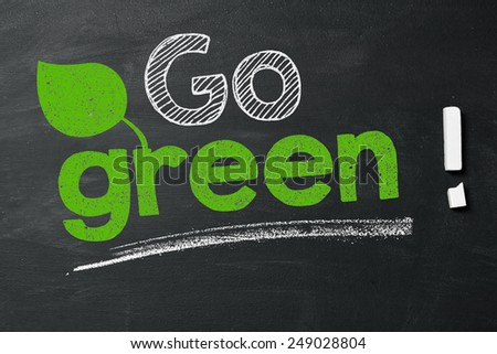 "Expression ""Go green!"" on blackboard - stock photo"