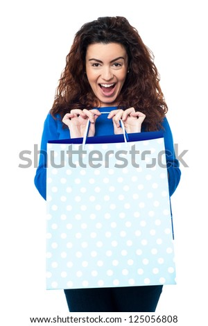 Expression of an excited woman displaying her shopping bags to the camera. - stock photo