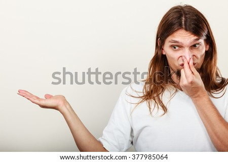 Expression of very bad smell. Young long haired sweaty man making hand gesture open empyt hand for product. Sweating concept. - stock photo