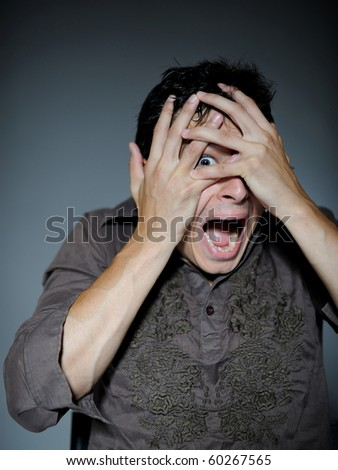 Expressions. Handsome young man feeling fear with open mouth and closing eyes with hands - stock photo