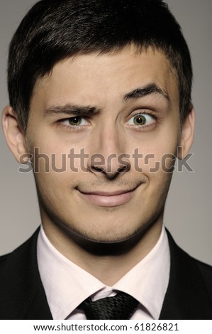 Expressions - Young handsome funny business man . studio shot - stock photo