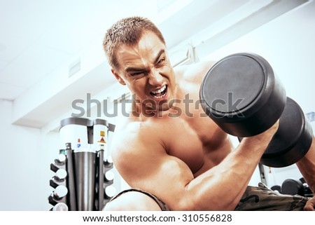 Expressive athletic man working out with dumbbells in a gym.  - stock photo