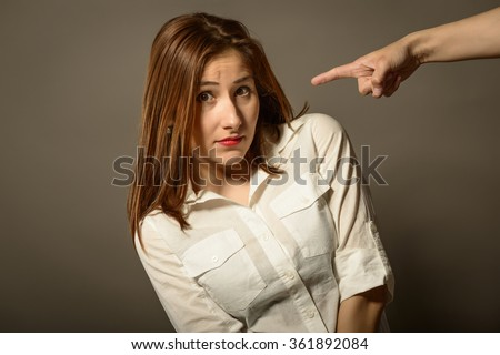 Expressive business woman looking at camera while someone is pointing finger on her, studio shot on gray background. Business woman getting intimidated after scolded by someone - stock photo