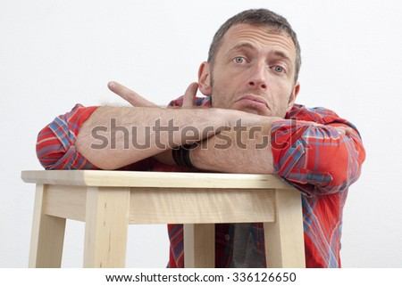 expressive casual man concept - careless middle age man with checked shirt leaning on wooden stool expressing depression and frustration,white background - stock photo