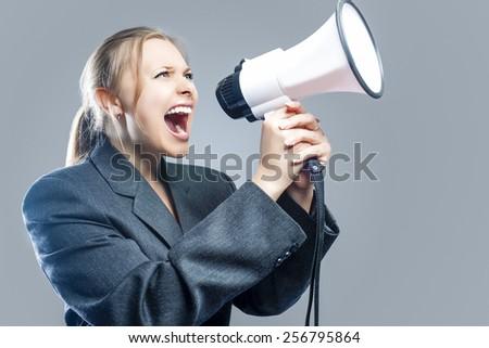 Expressive Caucasian Blond Female Screaming Using Big White Megaphone. Against Gray Background. Horizontal Image Composition - stock photo