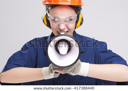 Expressive Caucasian Female Worker Posing with Megaphone and Wearing Hardhat for Protection. Horizontal Image Composition - stock photo