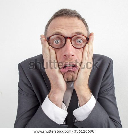 expressive corporate man concept - shocked middle age businessman expressing surprise and disappointment with humor,wide angle on white background - stock photo