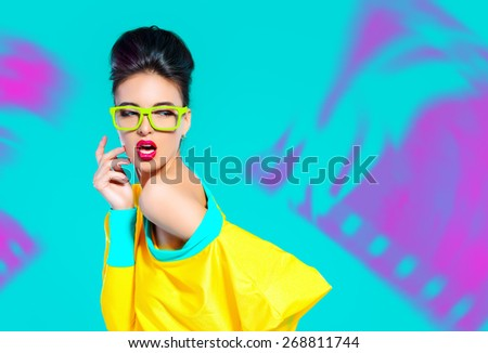 Expressive fashion model posing in vivid colourful clothes. Bright fashion. Optics, eyewear. Studio shot. - stock photo