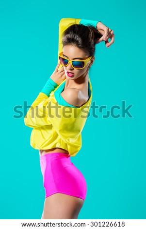 Expressive fashion model posing in vivid colourful clothes. Bright fashion. Optics, eyewear. Studio shot. - stock photo