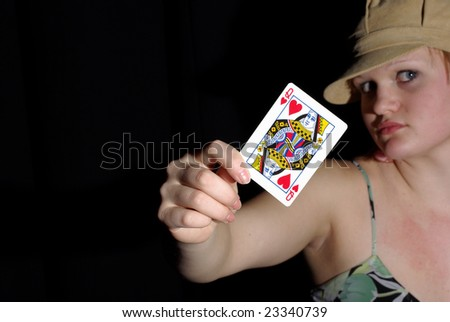 Expressive girl holds queen of hearts up. focus on card - stock photo