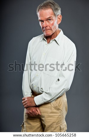 Expressive good looking senior man against grey wall. Funny and characteristic. Well dressed. Studio shot.