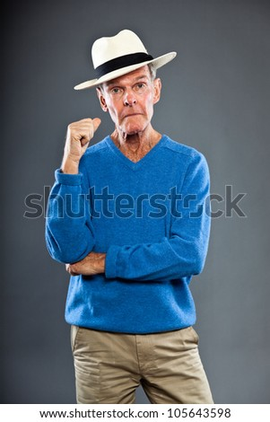 Expressive good looking senior man against grey wall. Wearing hat. Funny and characteristic. Well dressed. Blue sweater. Studio shot.