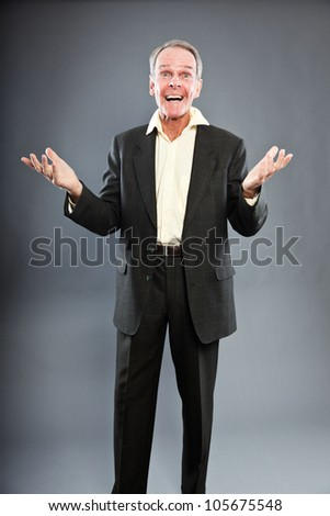 Expressive good looking senior man in dark suit against grey wall. Funny and characteristic. Well dressed. Studio shot. - stock photo