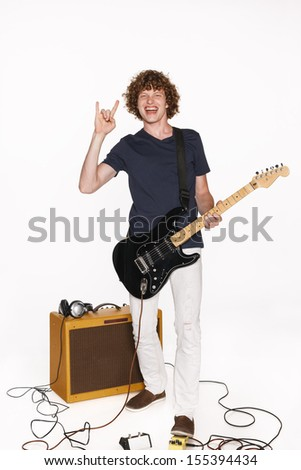 Expressive guitarist in full length playing his guitar passionately showing sign, isolated on white - stock photo